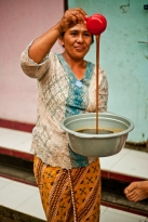 Ibu Juli proudly showing her fresh palm syrup, produced on a wood fire.